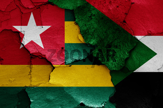 flags of Togo and Sudan painted on cracked wall
