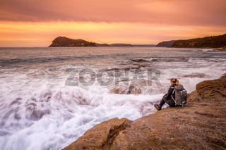 Woman sits by the ocean watching the waves flow back and forth