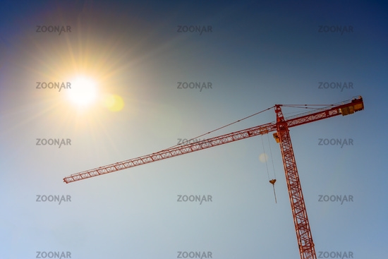 Industrial crane and sun on blue sky background