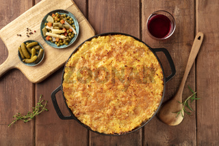 Homemade Shepherd's pie with pickles and wine on a rustic background, overhead shot