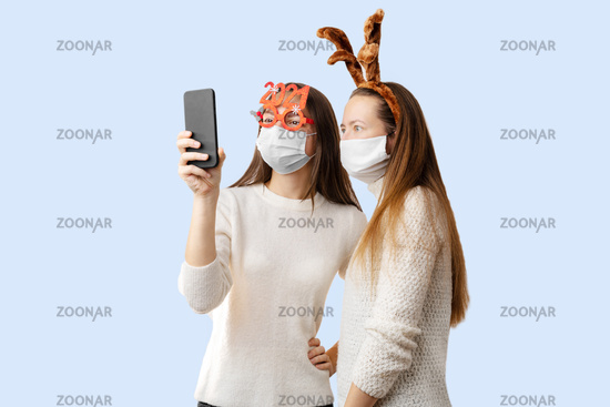 2 young girls or young woman with santa hat and face mask doing online video call. Quarantine christmas