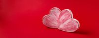 Two valentine hearts made of paper mache on red background. Symbol of love and holiday Valentine's Day.