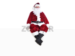 Senior man in traditional Santa Claus Suit sitting on a white wall.  Isolated on white with copy space.