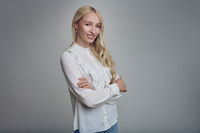 Young smiling blond woman with her arms folded