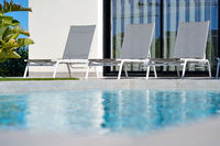 On poolside empty sunbeds at summer sunny day