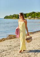 happy woman with picnic basket walking along beach