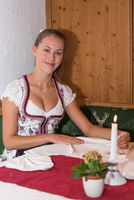 attractive waitress in a dirndl dress folds cloth napkins