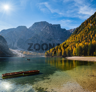 Sunshiny autumn peaceful alpine lake Braies or Pragser Wildsee. Fanes-Sennes-Prags national park, South Tyrol, Dolomites Alps, Italy, Europe. People are unrecognizable.