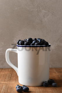 Blueberry Still Life. A white mug filled with fresh picked Blueberries on a wood table. Vertical format with copy space.