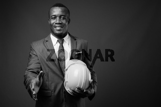 Young African businessman with hardhat against gray background
