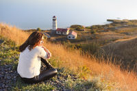 Young woman with near the Lighthouse and blue sea on background