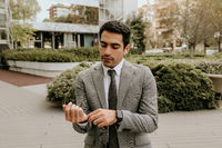 Confident businessman wearing grey suit and posing outdoors.