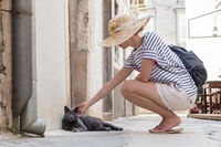 Female tourist woman wearing big straw hat on summer vacation in ald traditional Mediterranean town, squating on old stone pedestrian street and caressing lazy gray cat lying in front of house