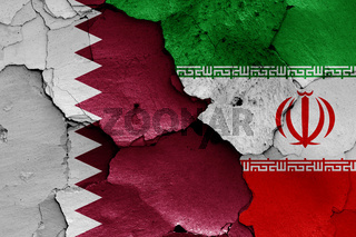 flags of Qatar and Iran painted on cracked wall