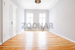 empty apartment room with wooden floor after renovation