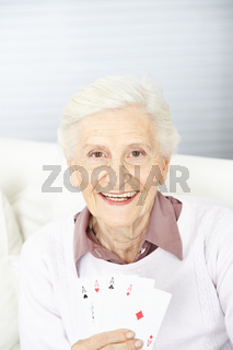 Seniorin hält vier Asse in der Hand