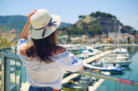 Rear view woman wear hat pose on Denia castle background. Spain