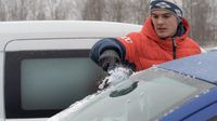 a young man clears the car glass of snow, a young man clears snow from a car