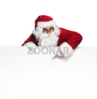 Happy Santa Claus pointing in blank wall with copy space