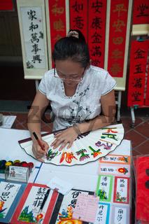 Singapur, Republik Singapur, Eine Kalligraphin verziert einen Handfaecher mit chinesischen Schriftzeichen und Bildern