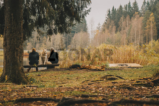 A couple sits by a tree with a dog, at the lake.