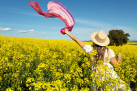 Woman in whte dress and floating scarf in canola field