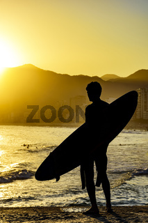 Surfer silhouette with his longboard looking at the Iapnema beach