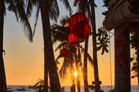 Boracay, Philippines - Jan 27, 2020: Sunset on Boracay island. Sailing and other traditional boats with tourists on the sea against the background of the setting sun. Tourists are sitting on the beach and among the palm trees looking at the setting sun.