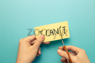 I can do it. Positive motivation concept. Remove 't' from the word 'I can't' with scissors