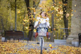 Young beautiful woman rides a bicycle in an autumn park under falling leaves.