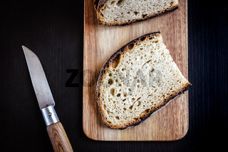 Traditional French country bread slices and pocket knife on a cutting board