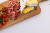 Cheese, ham and cherry tomatoes on wooden board on white background