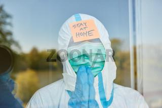 Klinikpersonal mit Stay at Home Botschaft in Fenster