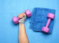 female hand in a pink sports glove holds a purple one kilogram dumbbell