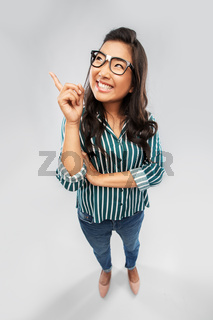 smiling asian student woman pointing finger up