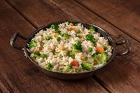 Vegetable rice with broccoli, carrots and green peas, in a frying pan on a rustic wooden background