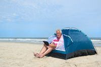 Man with digital tablet camping in shelter at the beach