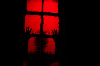 Silhouette of person touching window in dark