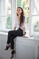 Beautiful brunette sitting by the window