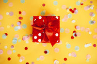 Red gift box and colorful confetti on yellow background