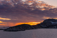 Glorious sunset over norwegian coast with snow covered rocks and dense clouds seen from open sea