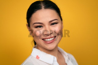 Pleasant looking glad Asian woman looks in camera, has toothy smile, wears casual clothing, isolated on yellow background. Human emotions, facial expression concept. Facial expressions, feelings