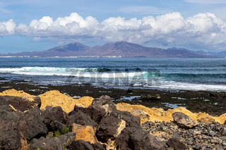 Panoramic view at the coastline in the natural park of Jandia (Parque Natural De Jandina) on canary island Fuerteventura with gravel, lava rocks and rough sea with waves and mountain range in the background