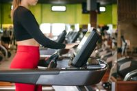 Woman point to button of speed control of treadmill in fitness center, set up program before workout.