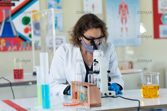 Female teacher wearing face mask and protective glasses using microscope in laboratory