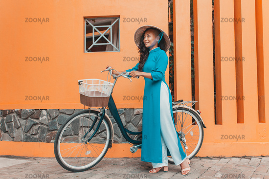 Young woman in traditional vietnamese dress with bicycle walking on street