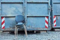 Stühle als Sperrmüll vor Bauschuttcontainer auf Industrie Gelände