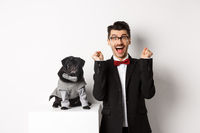 Animals, party and celebration concept. Happy young man in suit and puppy in pet cosume standing over white background, dog owner rejoicing and triumphing