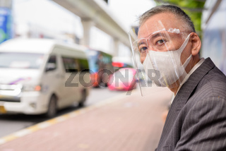 Mature Japanese businessman with mask and face shield sitting at the bus stop
