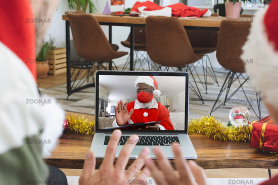 Rear view of man and son in santa hats waving while having a videocall with santa claus wearing face